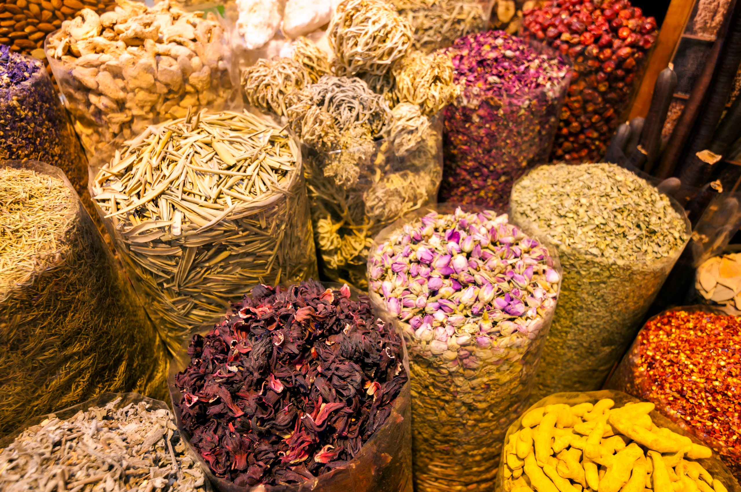 Amazing traditional souk market in Dubai creek district Deira with different baskets full of spices, Dubai, United Arab Emirates.