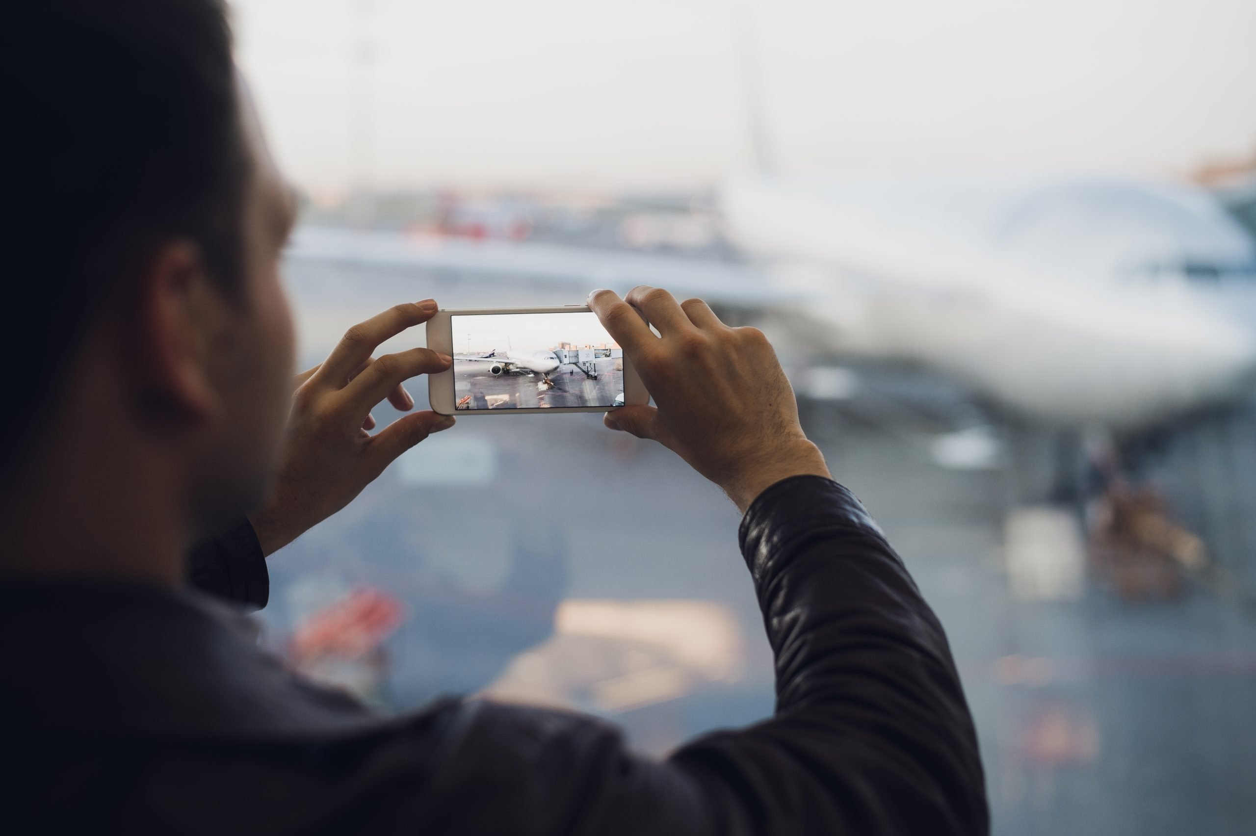 Man hand take picture of airplane using cellphone. Tourism concept photo.