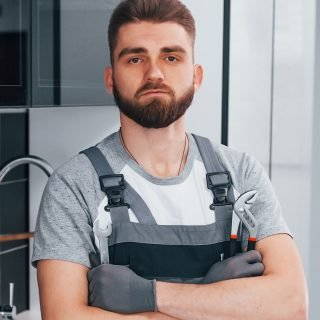 Young professional plumber in grey uniform standing on the kitchen.